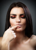 Sexy brunette with finger in mouth — Stock Photo