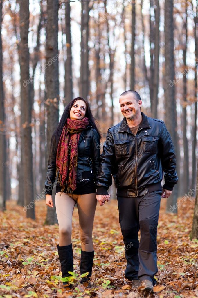 Full length portrait of a happy couple walking in the woods while holding hands — Stock Photo #16817081