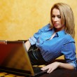 Young business lady with laptop in bed — Stockfoto