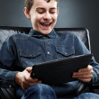 Stock Photo: Cheerful child playing on tablet
