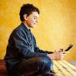 Stock Photo: Young boy playing on tablet