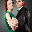 Close-up of charming young couple dancing tango over gray backgr — Stock Photo