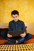 Young boy reading on digital tablet — Stock Photo