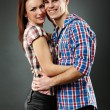 Closeup of cheerful young couple embracing - Stockfoto