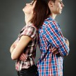 Portrait of sad young couple standing back to back — Stockfoto