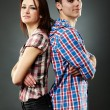 Happy young couple standing back to back over gray background — Stockfoto