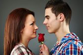 Young man offering a rose to the woman he loves — Stock Photo