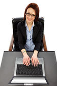 Charming businesswoman with laptop in front, looking up — Stock Photo
