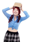 Happy young schoolgirl putting a pile of books on her head — Stock Photo