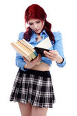 Young schoolgirl browsing through a stack of books — Stock Photo