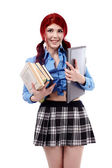 Young schoolgirl holding a pile of books and a laptop — Stock Photo