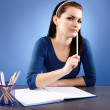Thoughtful young student sitting at her desk — Stock Photo #23794477