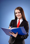 Happy businesswoman holding a notebook — Stock Photo