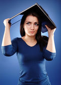 Stressed woman covering her head with her laptop — Stock Photo