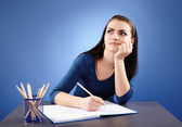 Young pensive student sitting at her desk — Stock Photo