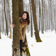 Woman hiding behind a tree trunk in the winter — Stock Photo