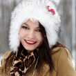 Beautiful woman wearing fur hat in the forest in the winter - Foto Stock