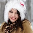 Beautiful woman wearing fur hat in the forest in the winter - Stok fotoğraf