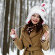 Beautiful womwearing fur hat in forest in winter — Stock Photo #23915837
