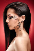 Beautiful brunette with facial tattoo — Stock Photo