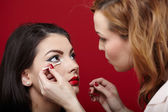 Woman having makeup applied by makeup artist — Stock Photo
