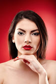 Beautiful glamour brunette on red background — Stock Photo