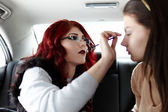 Woman having makeup applied on the backseat of the car — Stock Photo
