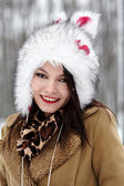 Beautiful woman wearing fur hat in the forest in the winter — Stock Photo