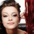 Beautiful woman having makeup applied by makeup artist — Stock Photo