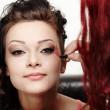 Beautiful woman having makeup applied by makeup artist — Stock Photo