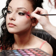 Beautiful woman having makeup applied by makeup artist — Stock Photo #25423147