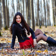 Beautiful woman sitting in the woods — Foto de Stock