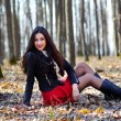 Beautiful woman sitting in the woods — Stockfoto