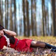 Beautiful woman laying in the woods — Stock Photo