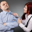 图库照片: Businesswoman pulling businessman's necktie