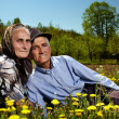 Old couple sitting in a dandelion field — Stock Photo