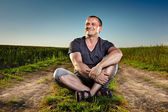 Young man sitting on a country road — Stock Photo