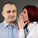 Businesswoman whispering in her boss' ear — Stock Photo