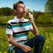 Boy blowing dandelion seeds — Stock Photo