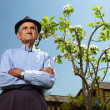 Senior farmer with an apple tree — Stock Photo #26658289