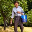 Stock Photo: Old farmer fertilizing in orchard