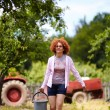 Stock Photo: Farmer lady with bucket in orchard