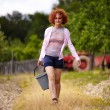 Farmer lady with a bucket in an orchard — Stock Photo