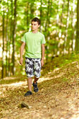Teen walking through a forest — Stock Photo