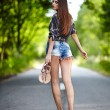 Sexy woman walking along the road — Stock Photo