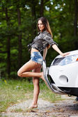 Sexy woman leaning on a car — Stock Photo