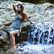 Woman sitting near a waterfall — Stock Photo