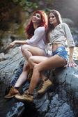 Attractive women standing on the rocks — Stock Photo