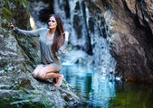 Sexy woman sitting on the mountain rock — Stock Photo