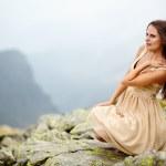 Elegant woman sitting on the rocks — Stock Photo #32086763
